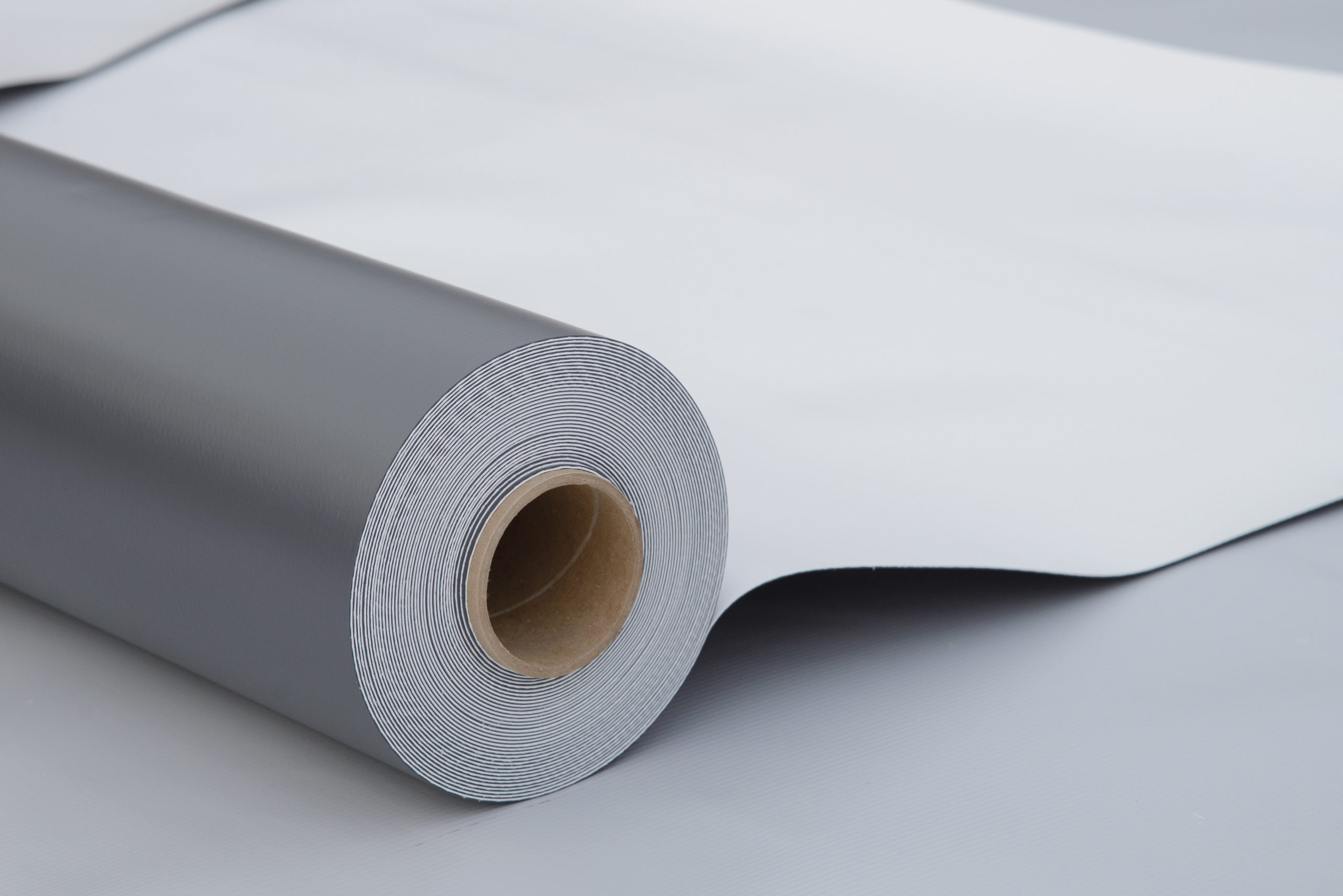 Waterproofing and insulation at construction site, opened pvc membrane roll lying on roof closeup. Copy space for your text